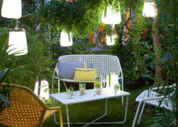 Lounge im Garten mit Möbeln aus Metall in Weiss und bunt